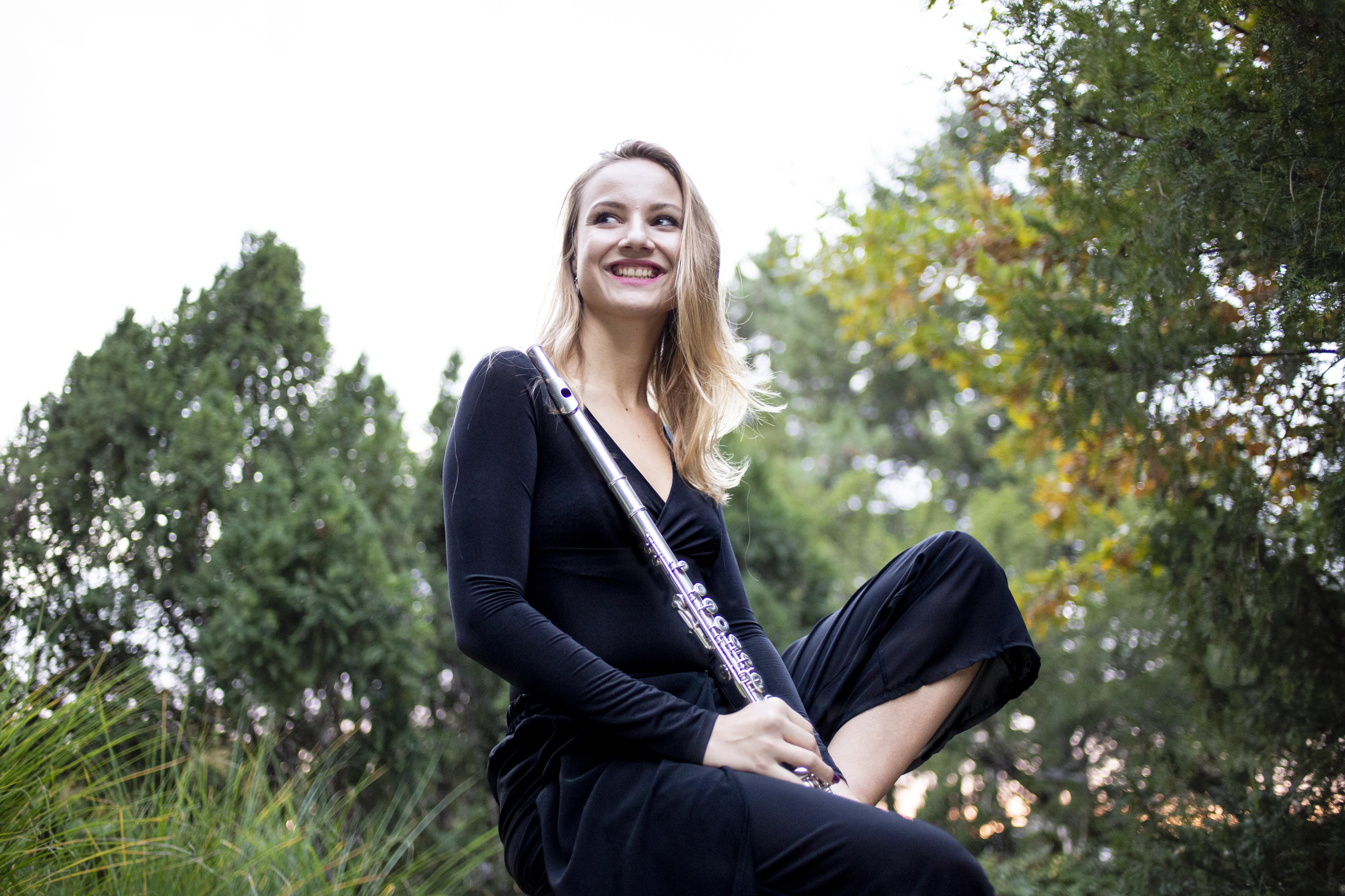 Ács Dominika fuvolával a kezében mosolyogva ül a fűben fekete ruhában
