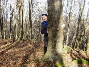 Színes Ilona egy fa mögül kukucskál egy erdőben kék sálban